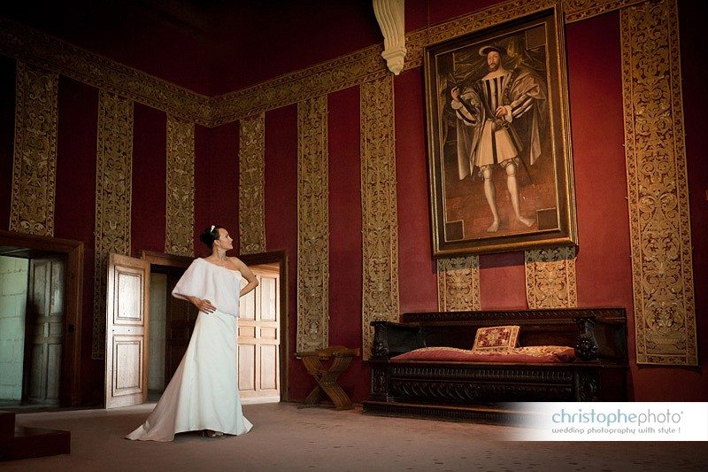 Bride posing in front of a portrait of French King François the first in Chateau de Chambord, France. Directed by wedding photographer france