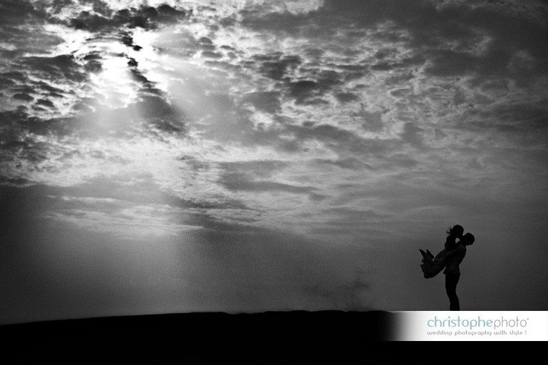 Silhouette of the couple fooling around and jumping in each other's arms in the sand dunes near Dubai and Abu Dhabi UAE.