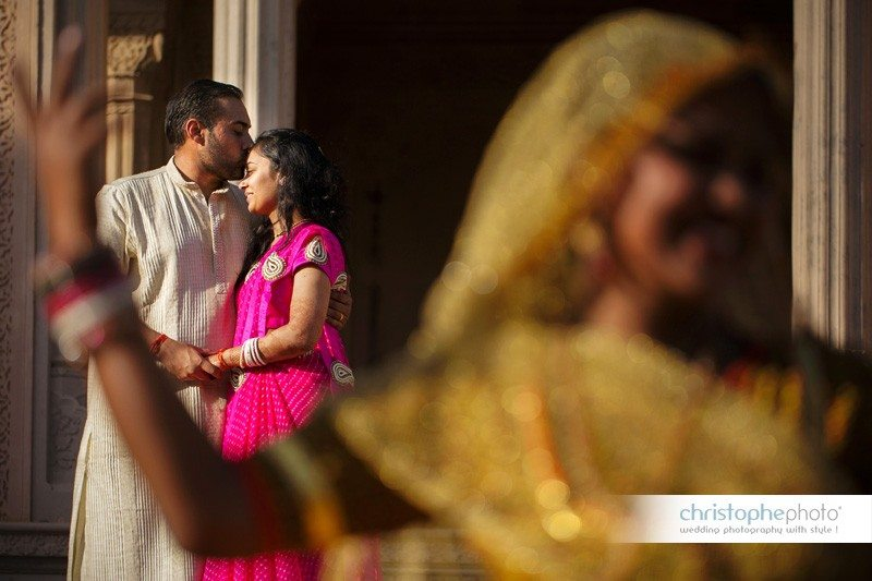 cute portrait of groom kissing the bride's forehand in front of rajasthani dancers