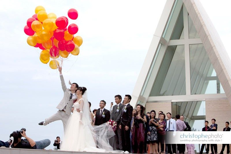 Bride and Groom fooling around with balloons after the catholic ceremony. Photo taken by Wedding Photographer Bali