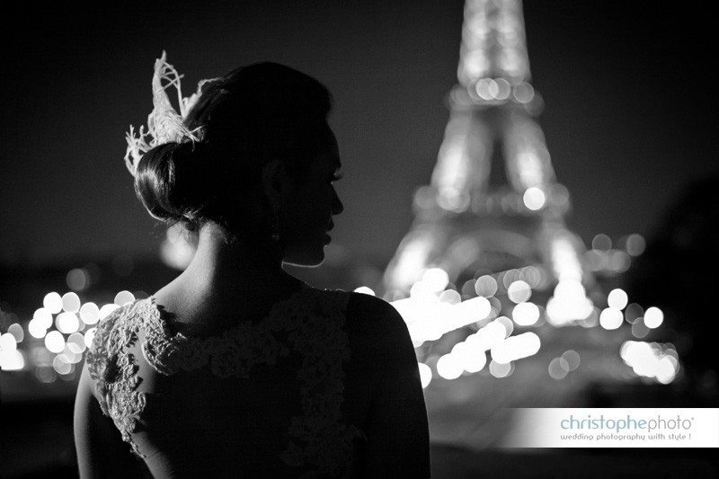 Bride posing at nightime with the Eiffel Tower in the background. Directed by Wedding Photographer Paris