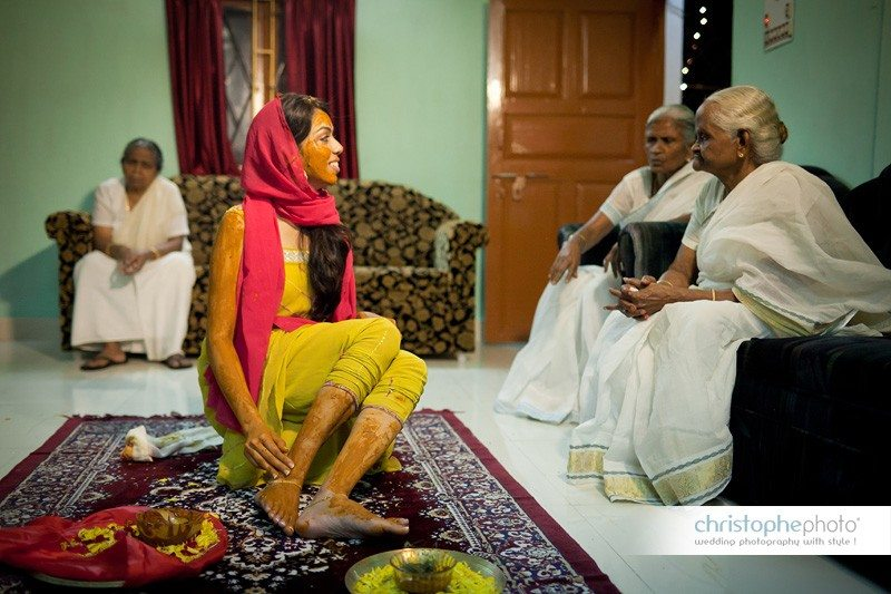 The bride-to-be facing her grandmas during the tumeric ceremony at the house where she grew up.